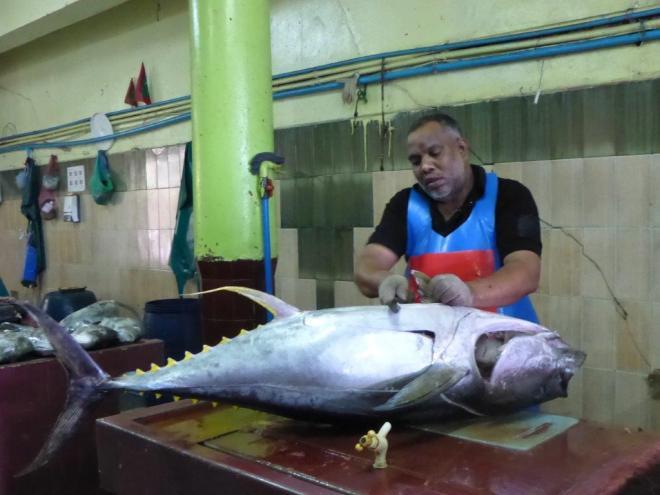 Fishmonger preparing a tuna at the fish marked in Male, the Maldives 2