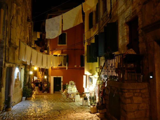 An elderly woman watching over her street in the old town of Rovinj, Croatia