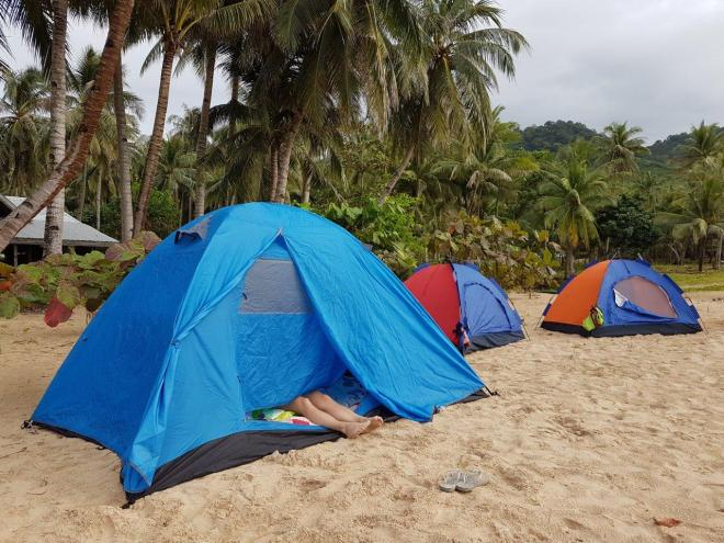 Tenting at the beach by a village north on Palawan. Three day expedition with El Nido Paradise from El Nido to Coron. Philippines.
