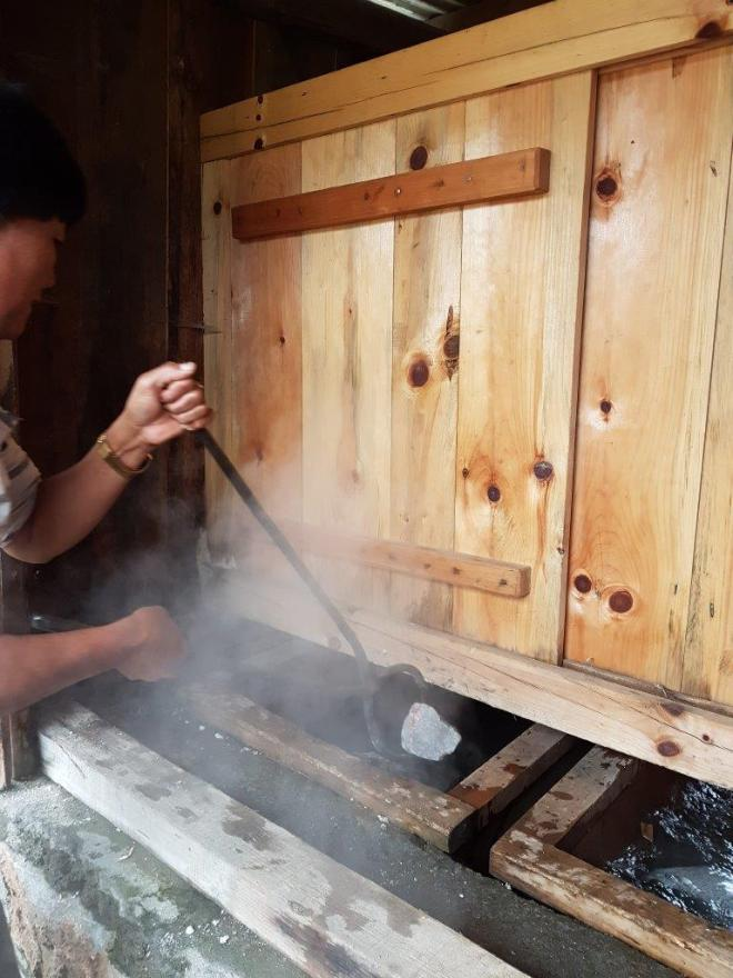 Putting the hot stones from the fire into the hot stone bath. Paro, Bhutan.