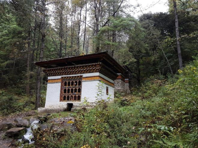 Three houses with prayer wheels rotated by the running stream.